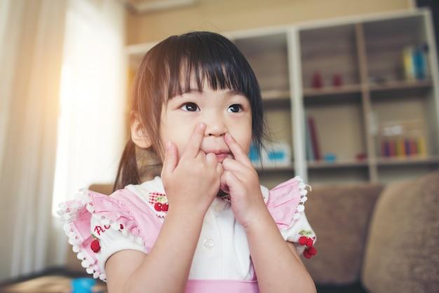 Portret van weinig aziatisch meisje dat in haar huis speelt