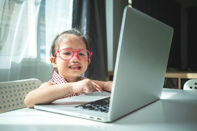 Portret van weinig aziatisch meisje met laptopcomputer voor online toepassing thuis studeren. homeschooling, online leren of onderwijsconcept