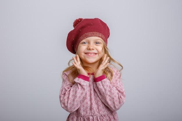 Portret van weinig blondemeisje in baret dat op witte achtergrond wordt geïsoleerd