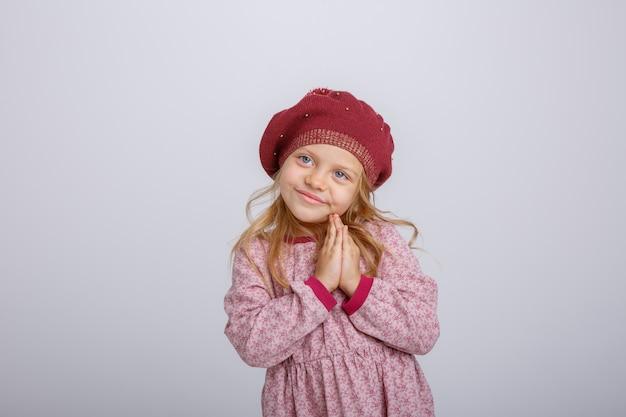 Portret van weinig blondemeisje in baret die hoop vragen die op witte achtergrond wordt geïsoleerd