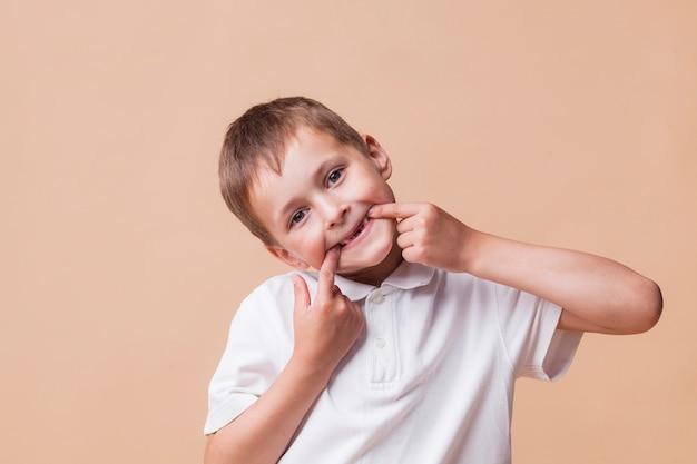 Portret van weinig jongen die camera bekijkt en op beige achtergrond plaagt