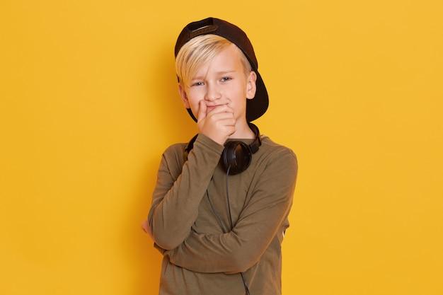 Portret van weinig jongen die zwart glb, het leuke kerel stellen geïsoleerd over geel, mannelijk jong geitje dragen die mond behandelen met handen