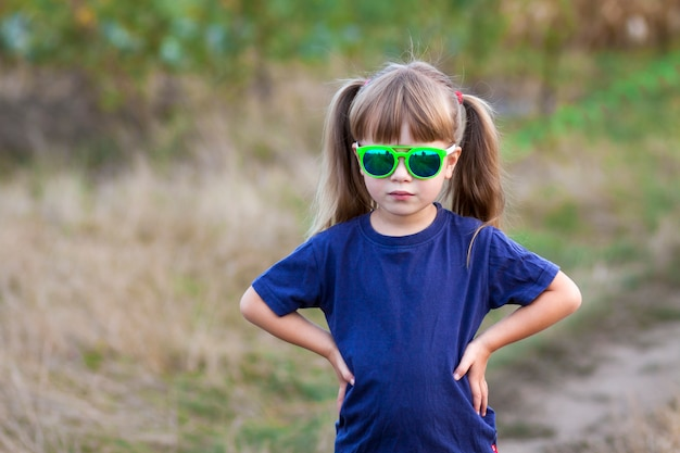 Portret van weinig modieus meisje in groene zonnebril in openlucht