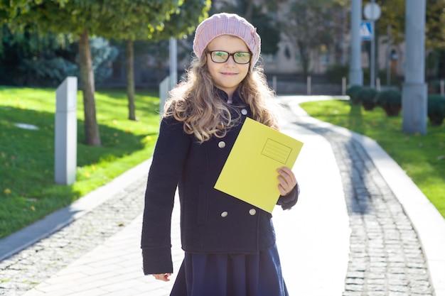 Portret van weinig schoolmeisje met notitieboekjes