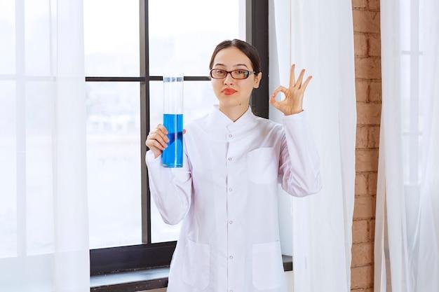 Portret van wetenschappervrouw in laboratoriumjas die chemische blauwe vloeistof houdt en ok teken doet.