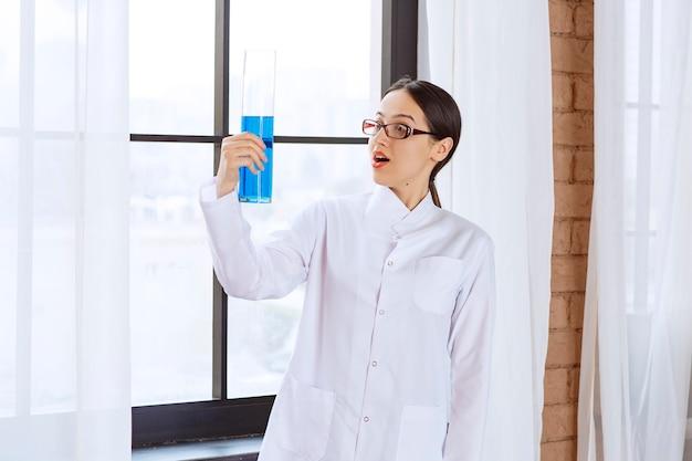 Portret van wetenschappervrouw in laboratoriumjas die chemische blauwe vloeistof houdt.