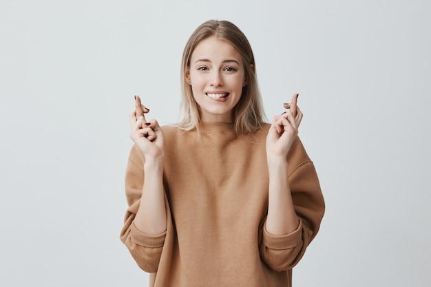 Portret van wishful jonge vrouw in casual kleding met blond geverfd haar, kruist haar vingers, bijt op haar onderlip, nerveus voor belangrijke gebeurtenis. lichaamstaal