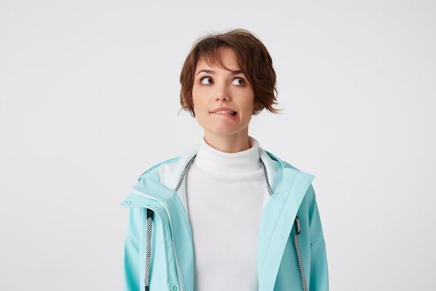 Portret van wishful kortharige jongedame in witte golf en lichtblauwe regenjas, staat op witte achtergrond, bijt lippen en kijkt weg.