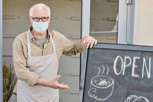 Portret van witharige volwassen eigenaar van winkel of café wijzend op open uithangbord
