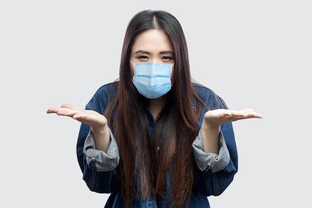 Portret van woede brunette aziatische jonge vrouw met chirurgisch medisch masker in casual blauw denim jasje staande armen en vragen. indoor studio opname, geïsoleerd op een grijze achtergrond.