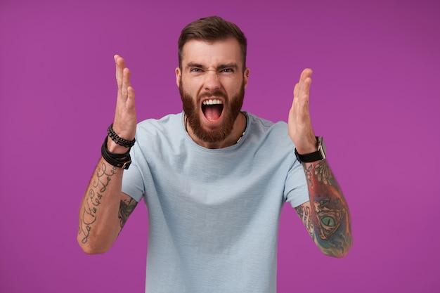 Portret van woedende bebaarde brunette man met tattooes palmen boos opheffen en gewelddadig schreeuwen met brede mond geopend, negatieve emoties tonen op paars