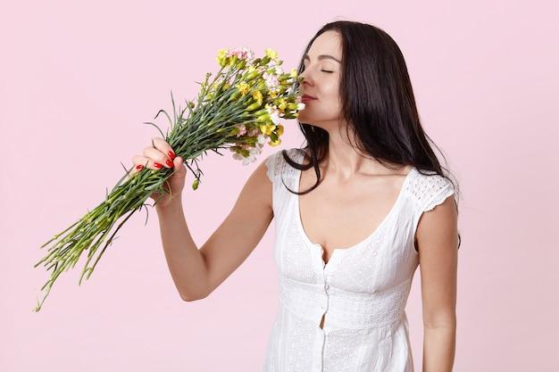 Portret van zachte donkerharige jonge dame, gekleed in witte jurk