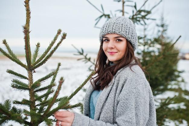 Portret van zachte vrouw in grijze laag en hoed tegen kerstmisboom openlucht.