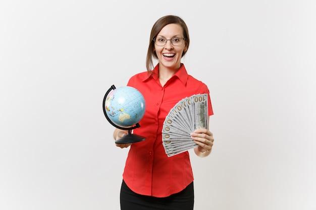 Portret van zakelijke leraar vrouw in rood shirt met globe veel dollars, contant geld geïsoleerd op een witte achtergrond. onderwijs onderwijzen in middelbare school universiteit, toerisme, studeren in het buitenland concept.
