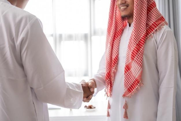 Portret van zakelijke moslimpartner hand schudden in de vergadering