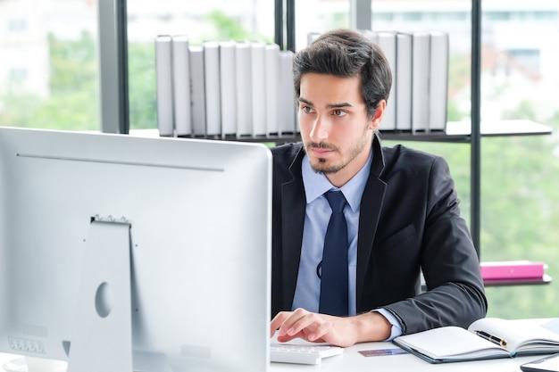 Portret van zakenman at office desk die computer met behulp van