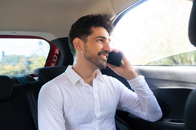 Portret van zakenman die aan de telefoon praat op weg naar zijn werk in een auto