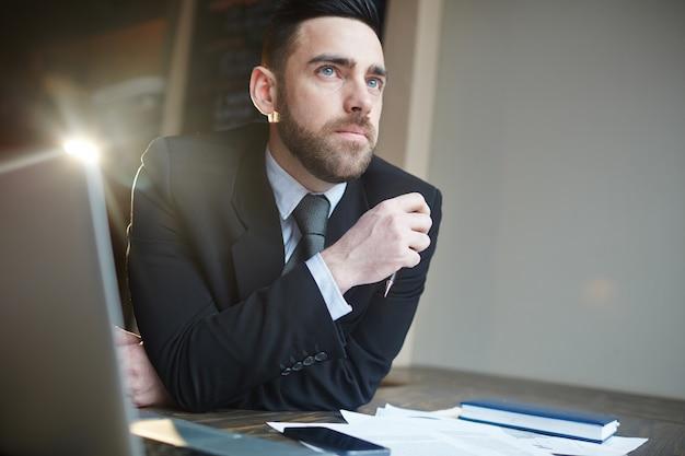 Portret van zakenman die bij bureau denkt