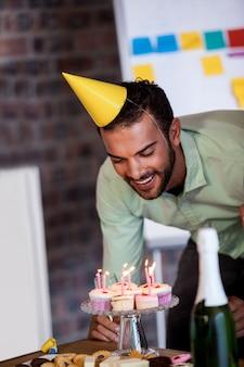 Portret van zakenman die de kaarsen voor zijn verjaardag uitblazen
