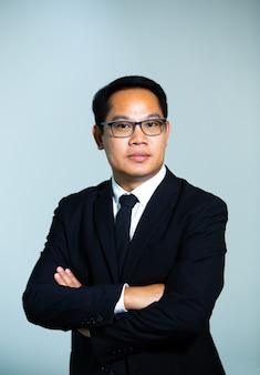 Portret van zakenman die een bril op een grijze achtergrond draagt. close-up gezicht van gelukkige succesvolle zakenman