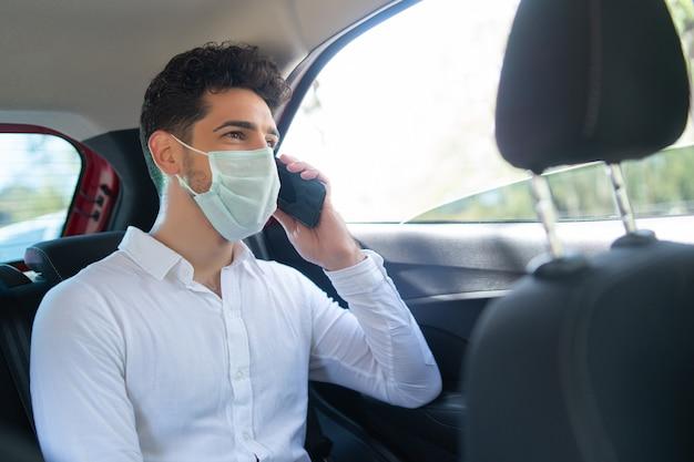 Portret van zakenman die gezichtsmasker draagt en over telefoon spreekt op weg om in een auto te werken. bedrijfsconcept. nieuw normaal levensstijlconcept.