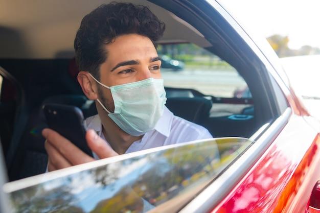 Portret van zakenman die gezichtsmasker draagt en zijn mobiele telefoon gebruikt op weg om in een auto te werken. bedrijfsconcept. nieuw normaal levensstijlconcept.