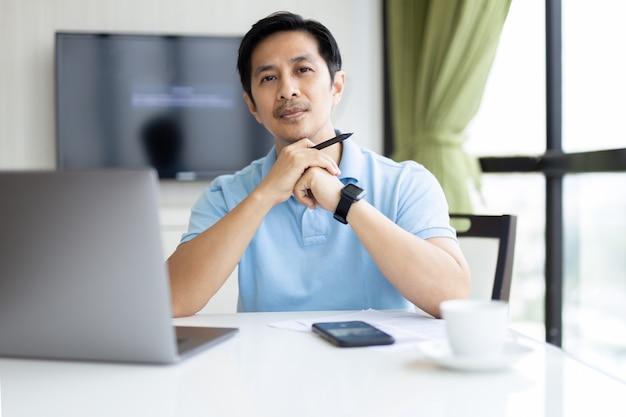 Portret van zakenman die op laptop op kantoor werkt.