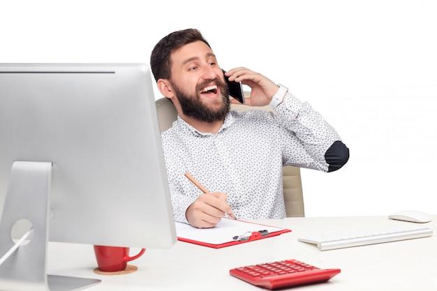 Portret van zakenman die op mobiele telefoon in bureau spreekt