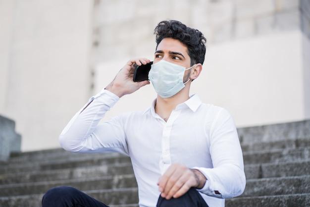 Portret van zakenman dragen gezichtsmasker en praten aan de telefoon zittend op de trap buiten