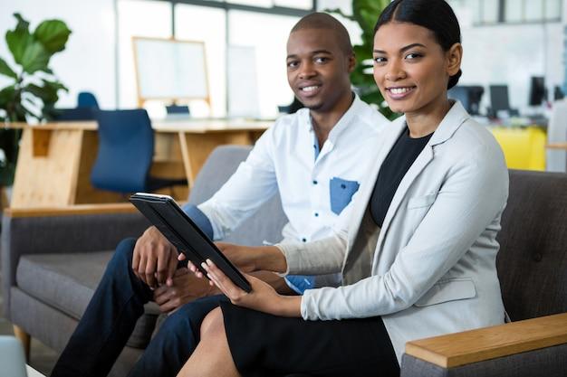 Portret van zakenman en een collega die over digitale tablet bespreken
