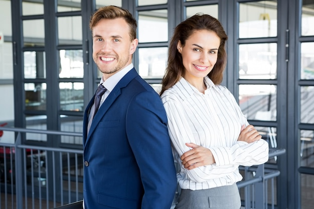 Portret van zakenman en onderneemster die in bureau glimlachen