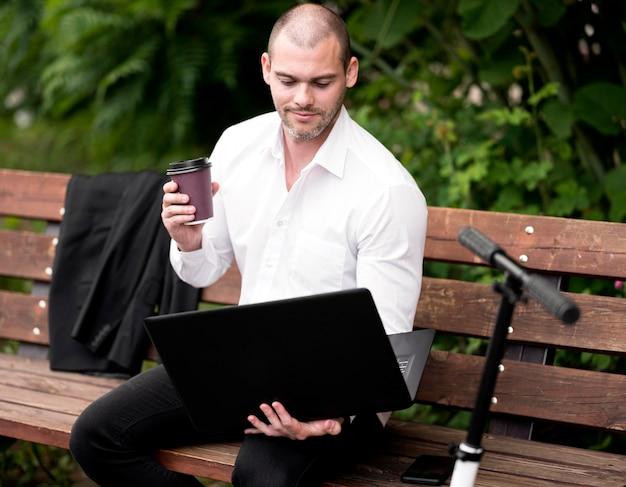 Portret van zakenman het doorbladeren laptop in openlucht