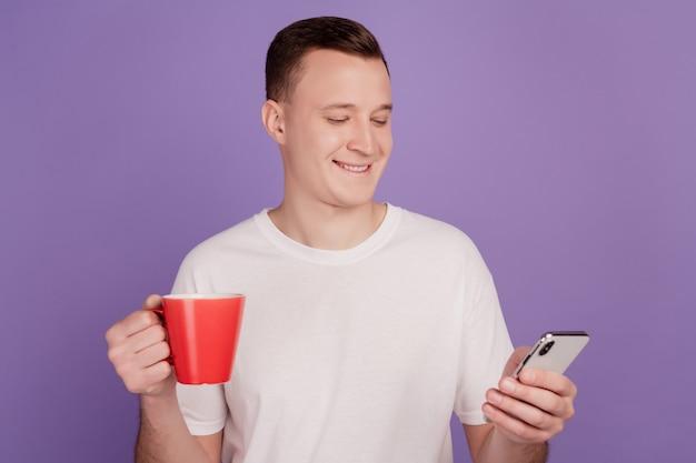 Portret van zakenman houdt kopje koffie kijk schermtelefoon op paarse achtergrond