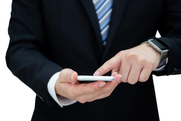 Portret van zakenman in formeel zwart kostuum dat op smartphones tikt