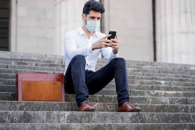 Portret van zakenman met gezichtsmasker en met behulp van zijn mobiele telefoon zittend op de trap buiten op straat
