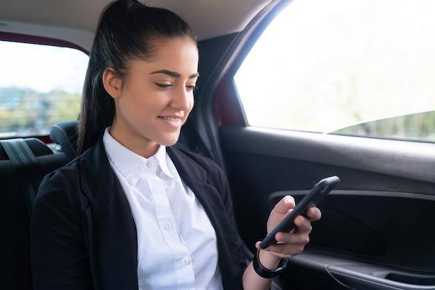 Portret van zakenvrouw die haar mobiele telefoon gebruikt op weg naar haar werk in een auto