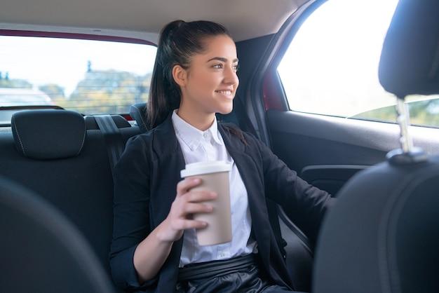 Portret van zakenvrouw die koffie drinkt op weg naar haar werk in de auto. bedrijfsconcept.