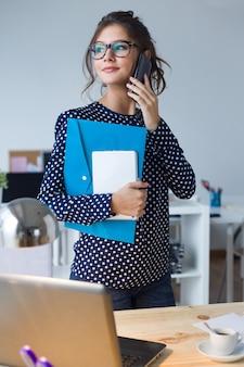 Portret van zakenvrouw die werkt met mobiele telefoon in haar kantoor.