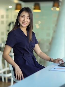 Portret van zakenvrouw glimlachen naar camera zittend op werktafel in kantoorruimte