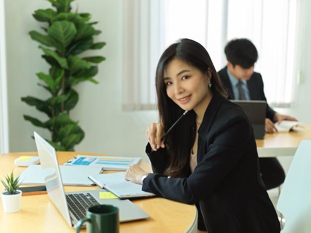 Portret van zakenvrouw glimlachen tijdens het werken met laptop en zakelijke papierwerk in kantoorruimte