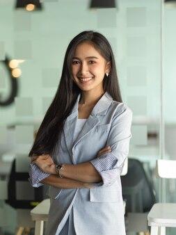 Portret van zakenvrouw glimlachend en armen gekruist staande in kantoorruimte