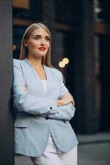 Portret van zakenvrouw in blauwe jas die bij de muur staat