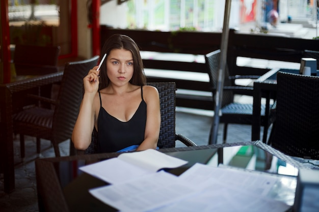Portret van zakenvrouw in brillen maken van aantekeningen in notitieblok aan tafel in restaurant