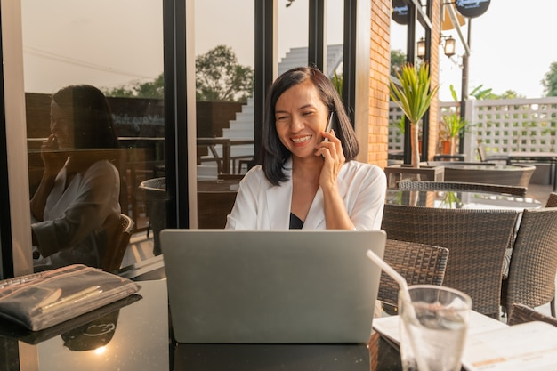 Portret van zakenvrouw in een café met behulp van een laptop en praten met mobiel