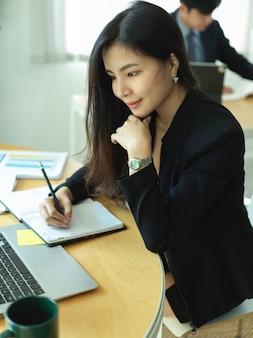 Portret van zakenvrouw in zwart pak te concentreren op haar werk in kantoorruimte