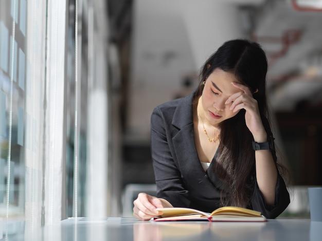 Portret van zakenvrouw leesboek op tafel in kantoorruimte