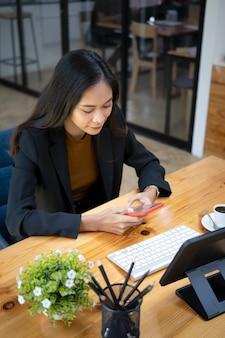 Portret van zakenvrouw met behulp van slimme telefoon zittend in de vergaderruimte.