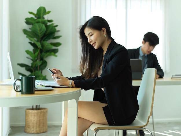Portret van zakenvrouw met behulp van smartphone terwijl u ontspant van het werk op de werkplek