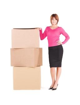 Portret van zakenvrouw met dozen over witte muur