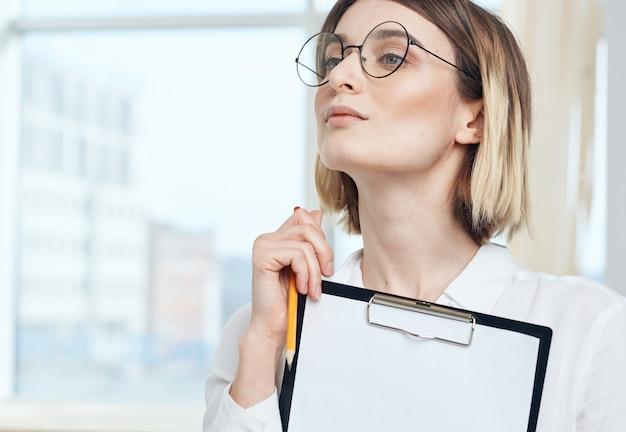 Portret van zakenvrouw met wit vel papier in de map financiën